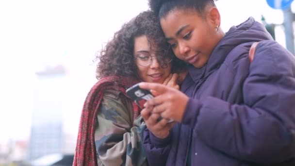 Two young women multiethic outdoor using smart phone  social network, wireless technology, wireless communication concept