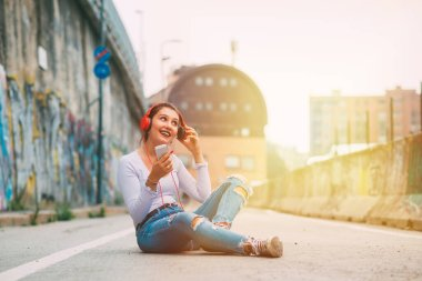 Young woman sitting outdoors listening music - Young woman enjoying music streaming smartphone