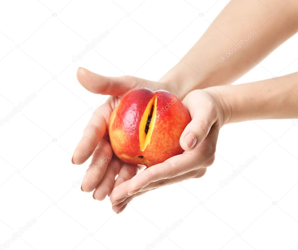 Woman hands hold peach with cute slice on white. Concept of intimate female part