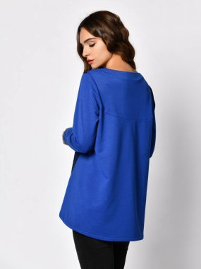 Young beautiful brunette woman posing in new casual blue blouse sweater
