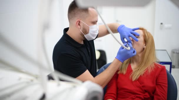Girl patient at dentist cabinet make oral hygiene dental treatment during surgery