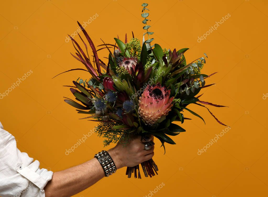 Man hand hold modern bridal bouquet with exotic flowers green leafs thistle eryngium on yellow background