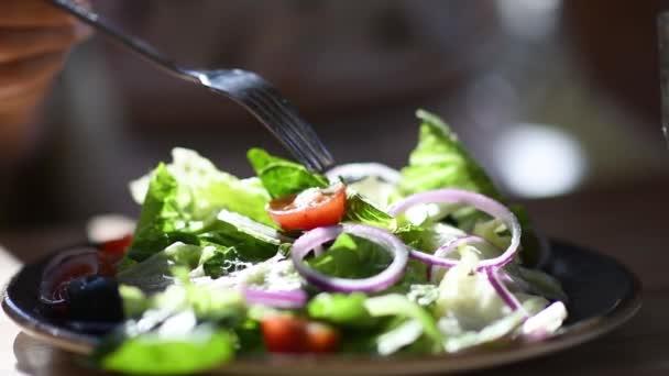 Ruka z closeup s vidličkou jíst čerstvý zeleninový salát pomalý pohyb