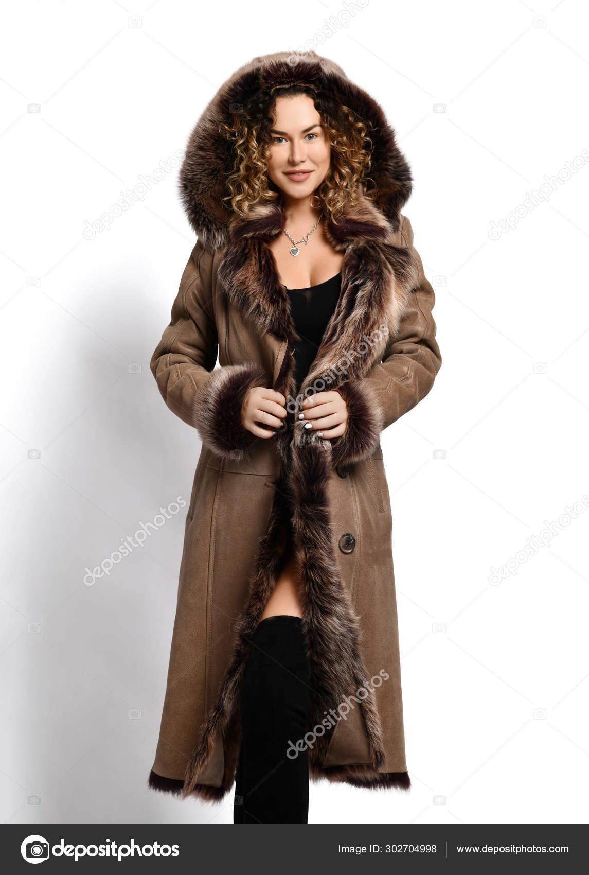 Femme rousse riche dans le body et le bas posant le manteau