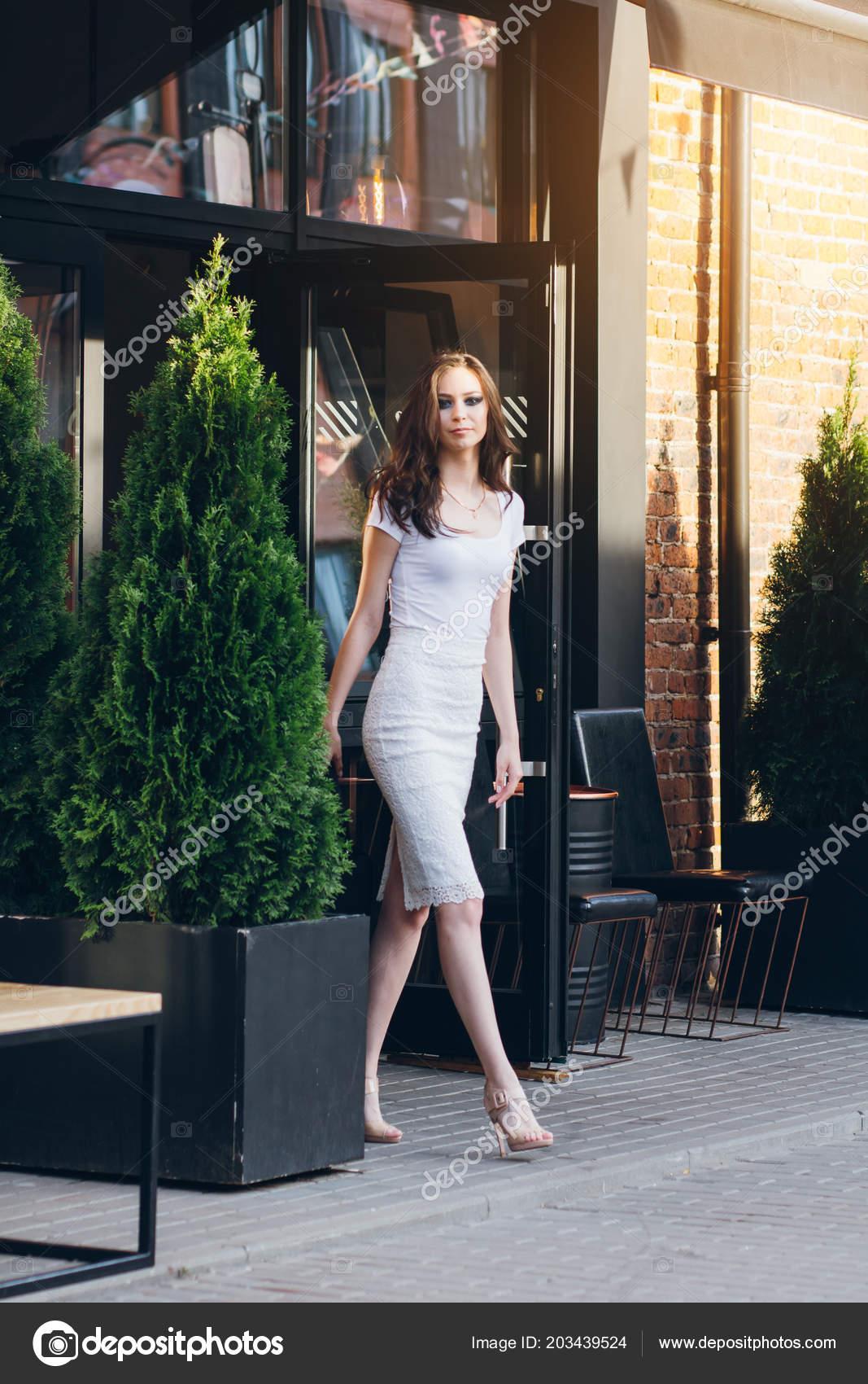 dd582a60f7ab Giovane bella ragazza castana con capelli lunghi in vestito bianco elegante.  Donna che cammina per le strade della città la sera al tramonto– immagine  stock