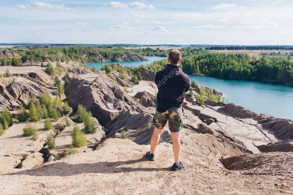 Abandoned sand quarry to the blue lake. Konduki, Tula region, Russia. A man looks into the distance. Toning.