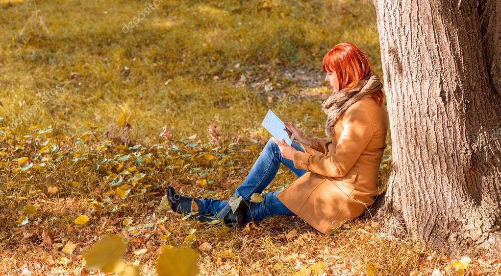 Fun in the autumn forest - Young woman using tablet outdoor