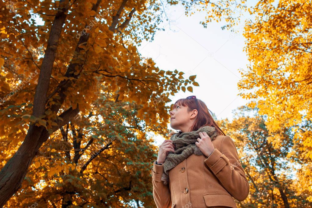Young ginger woman at beautiful autumn forest
