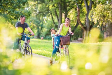 Happy active father and mother with kid on bicycles having fun in park. Happy family