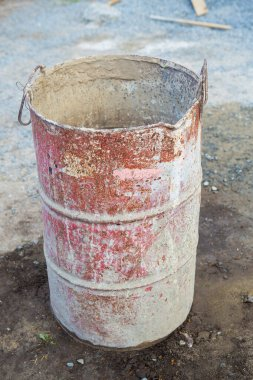 An old rusty metal barrel covered with multi-colored spots stands on the street. Everything for repair, construction