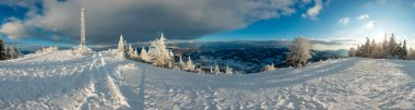 Winter evening sunshiny calm mountain panorama landscape with beautiful frosting trees and communication tower, footpath and ski track through snowdrifts on Carpathian Mountains slope, Ukraine.