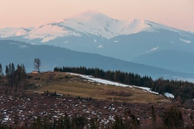 Early morning spring Carpathian mountains plateau landscape with snow-covered ridge tops in far, Ukraine.