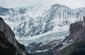 Summer Alps mountain landscape with glacier and snow covered rocky tops in far, Switzerland.