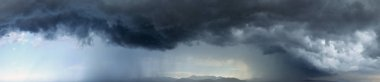 Stormy overcast sky and anger rain above mountains