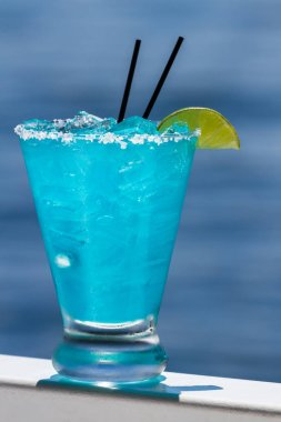 refreshing blue margarita served outside with a water background as a travel concept