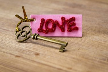Conceptual image using an old key with a pink tag with red glitter letters spelling the word love over a wooden background stock vector