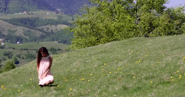 Krásná žena v šatech se těší glade horských květin