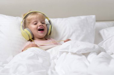 little child baby girl lying in white bed in headphones listening music with smartphone happy laughing smiling sheerful morning