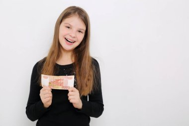 Russian teen girl holding 5000 rubles (five thousands roubles cash money of Russian Federation)