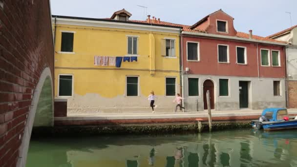 European teen girls are chatting outdoor at summer day in Murano, Veneto, Italy.
