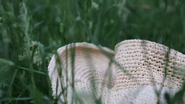 Kurze Filmaufnahmen von Strohhut im grünen Gras zur Sommerzeit. Ausgewählte Schwerpunkte. Hintergrund verschwimmen lassen. Bokeh.