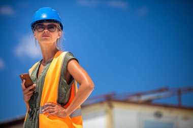 Female engineer architect with a  safety helmet and a cell phone in a building site planning new commercial residential project