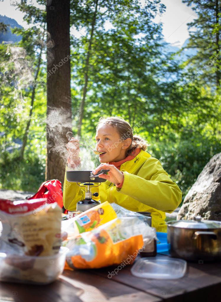 Female hiker/climber preparing supper on gas burner in a camp