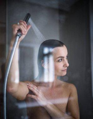 Woman taking a long hot shower washing her hair in a modern design bathroom