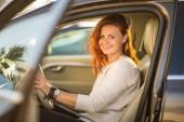 Hübsche, junge Frau am Steuer eines Autos - Einladung zum Reisen. Autovermietung oder Urlaub.