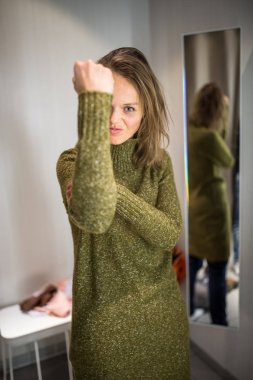 Young woman shopping happily in a fashion store, trying on some