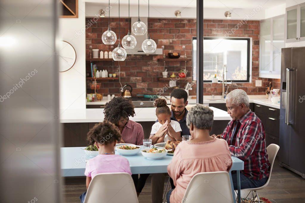family praying around table - 768×512