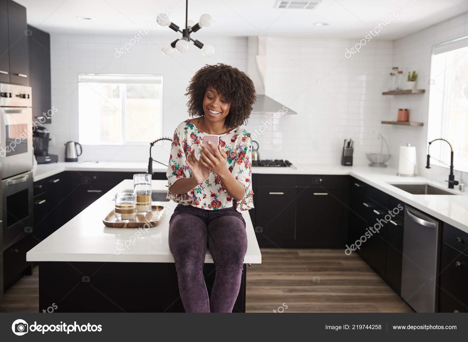 Frau Hause Sitzen Auf Kucheninsel Wahrend Mobiltelefon Stockfoto