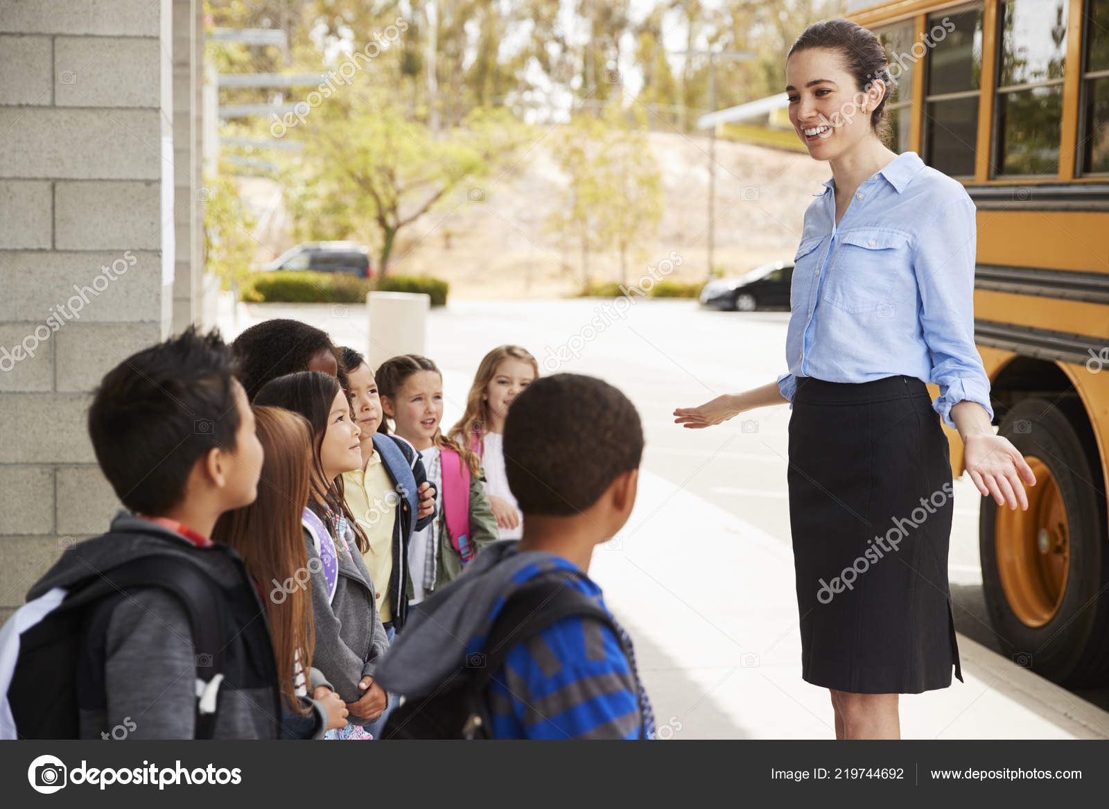school teacher talking kids get school bus stock photo