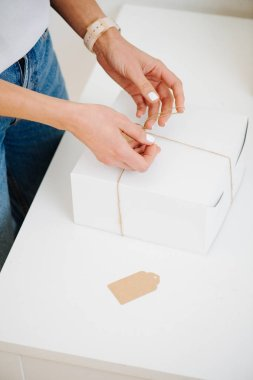 Woman in casual clothes is tying postal cardboard box, attaching tag at home