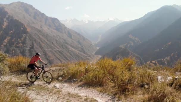 Muž jízda na kole na horské silnici střílel dron