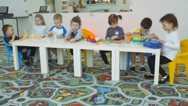 Childrens developing a game room. Emotions of young children during entertaining classes. Children build buildings from plastic and wooden geometric figures.