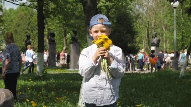 Pás karet svatého Jiří. Trikolorní červená, modrá, bílá. chlapec se táhne ke kameře kytice jasně žlutých květů. chlapec stojí na pozadí zelené zahrady a rozlišovací označení je připojen