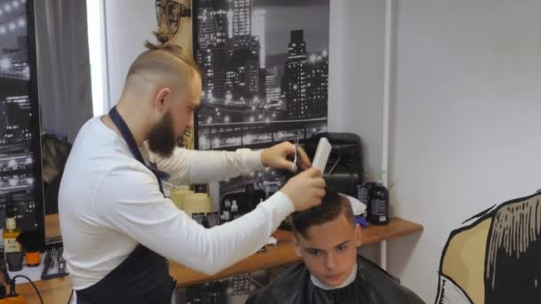 Hairdresser for men. Barbershop. A young guy gets a haircut and hair care service from a bearded man with a hair tied on his head. Cut hair head scissors with a comb. Funny hairdresser.