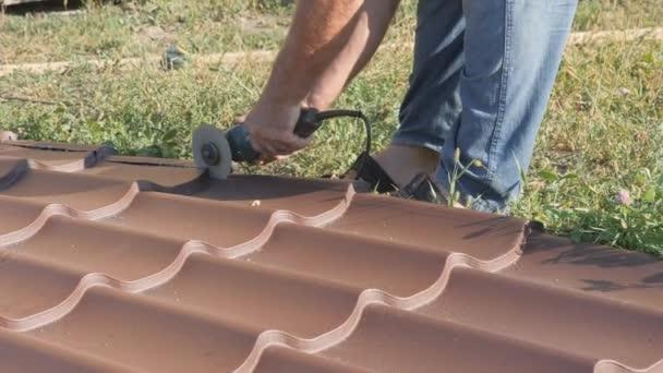 Arbeiten mit Dachmaterial. Dach aus Metall. Schneiden Profil Metall elektrische bulgarische. Funken fliegen unter dem Metallkreis des Handschneidewerkzeugs hervor. Dachpfannen liegen auf grünem Gras
