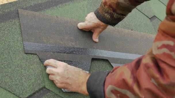 Oprava střechy obytného domu. Pokládka dlažby na měkké. částečné nahrazení poškozené střechy. Tečkou opravy. Odstranění ochranné fólie z lepidlo základní střešní krytiny