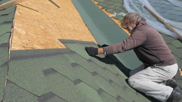 měkká Střecha šindele. Oprava střechy obytného domu. Pokládka dlažby na měkké. částečné nahrazení poškozené střechy. Tečkou opravy. Carpenter hodí kladivo a úlovky. Dělník