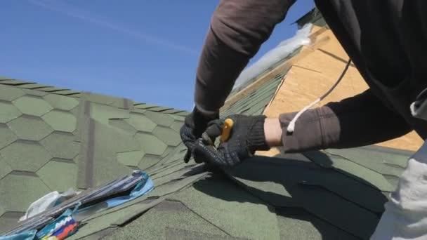 měkká Střecha šindele. Oprava střechy obytného domu. Pokládka dlažby na měkké. částečné nahrazení poškozené střechy. Tečkou opravy. Master uřízne přebytečnou střešní krytiny s nůžkami