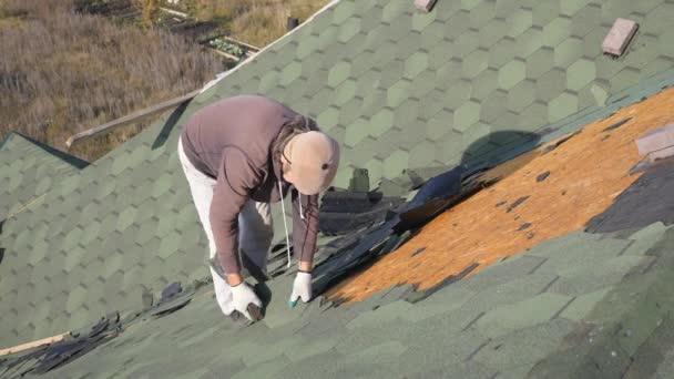 Demontáž měkké střechy. Francouzské zelené dlaždice. Pokrývač pracuje na šikmé střechy. Muž s vousy odtržení staré střešní krytiny z dřevěné desky s pomocí páčidlo. Stavební práce na