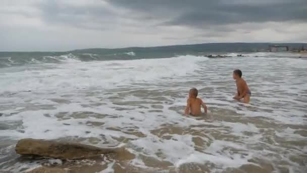 baby on the beach, in the maritime wave. Two boys on the golden sand playing in the surf.