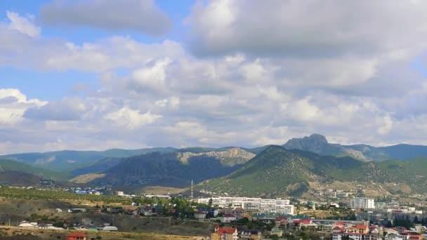 Janovské pevnosti, Sudak, Krym. Hory proti modré obloze s bílé mraky. Cirry narazíte na modré obloze. Pohled shora na město v horách, budovách a na silnici s kolem