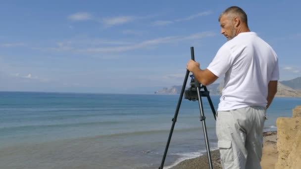 Filmaře střílí na pobřeží na fotoaparátu na stativ