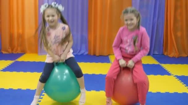 Childrens playroom. Little girls jump on the gymnastic balls.
