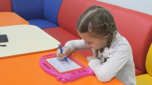 Childrens playroom. Studio entertainment for young children. Cute little girl paints on a magnetic blackboard special pen.