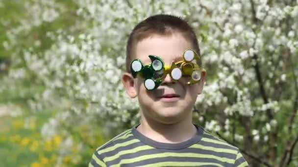Spinner auf der Brille dreht sich. Spaß auf der Straße. ein Kind auf dem Hintergrund blühender weißer Kirschblüten.