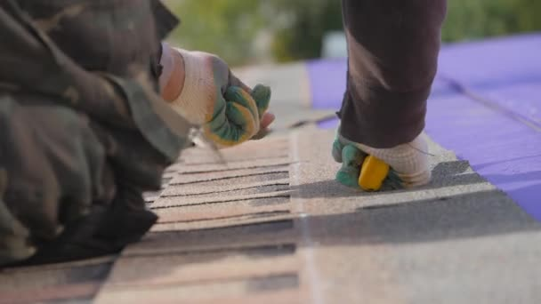 Položit měkkou střechu. Práce ve výšce. Upevnění plechu materiálu pomocí hřebíků a kladiva.